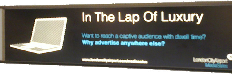 Photo of a commercial in London City airport saying 'In the lap of luxury - Want to reach a captive audience with dwell time? Why advertise anywhere else? - London City Airport Media Sales'